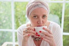 头巾的妇女喝从杯子的 库存图片