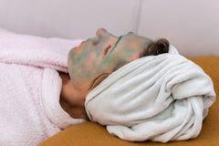 浴巾的妇女有在她的面孔的一个化妆面具的 免版税库存图片