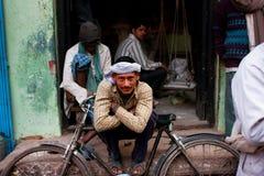 头巾的工作者休息倾斜在他在街道上的减速火箭的自行车 免版税库存图片