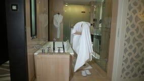 浴巾的欧洲性感的赤裸女孩在洗澡以后包裹有毛巾的湿头发 妇女穿上白色拖鞋,叶子 股票录像