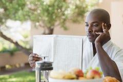浴巾读书纸和有早餐的人在大阳台 免版税库存图片