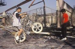 市内贫民区青年在被烧光的buil的骑马自行车 库存照片