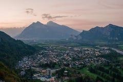 市的全景以瑞士阿尔卑斯为背景的坏Ragaz日落的 坏ragaz瑞士 库存照片