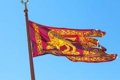 市的威尼斯式红色和金旗子威尼斯,意大利,飞过的狮子 库存照片