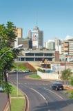 市的风景格兰德营 有一些大厦的城市在树、汽车通行和都市艺术之间 免版税库存照片