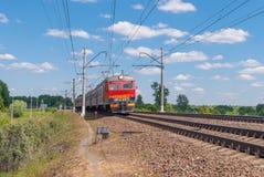 市郊火车移动由铁路在俄罗斯在一个晴天 图库摄影