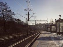 市郊火车驻地的孤独的人寒冷,冬天早晨 免版税库存照片