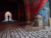 市Marakesh,红色墙壁,石头的路面的麦地那的老大厦,在距离曲拱和在它一个小人 图库摄影