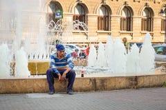 布加勒斯特,罗马尼亚- 28 04 2018年:在喷泉的无家可归的人就座在老镇布加勒斯特 免版税库存照片