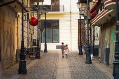 布加勒斯特,罗马尼亚- 28 04 2018年:街市老镇和餐馆狭窄的街道的两个罗马尼亚兄弟  免版税图库摄影