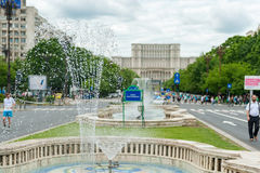 布加勒斯特,罗马尼亚- 2017年5月30日:与街道喷泉和空的街道的布加勒斯特都市风景 议会在背景中 免版税库存图片