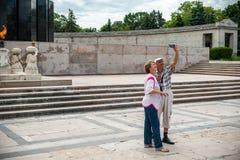布加勒斯特,罗马尼亚- 2017年5月14日:卡罗尔公园在布加勒斯特,罗马尼亚 陵墓在背景中 采取Selfie的成人 免版税库存图片