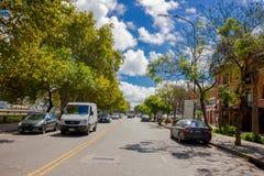 布宜诺斯艾利斯,阿根廷- 2016年5月02日:有树的精密街道在边路在一个晴天 免版税库存图片