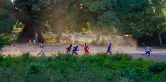 布巴克,几内亚比绍- 2013年12月11日:踢橄榄球或足球在土领域的未认出的小组人 免版税库存图片
