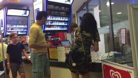 布德瓦,黑山- 2017年6月30日, 有长的腿的一个美丽的浅黑肤色的男人支付购买站在队中在结算离开的 股票录像