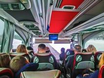 布拉格,捷克共和国- 2017年12月30日:游人坐在公共汽车上和看通过公共汽车窗口的小组 免版税库存照片