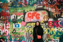 布拉格,捷克共和国 摆在为照片在著名附近约翰・列侬墙壁的中国妇女游人 墙壁充满 库存照片