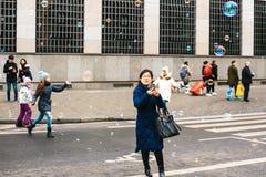 布拉格,捷克, 2016年12月24日:亚裔女孩旅游为照相的街道展示 儿童抓住肥皂泡 库存图片