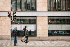 布拉格,捷克, 2016年12月15日 一个少妇站立在红绿灯在区的大厦旁边 库存图片