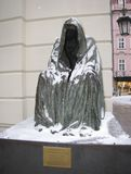布拉格,捷克2015年1月10日:在其中一条一件雨衣的有敞篷的追上的一个人的雕塑布拉格街道  信号 库存图片