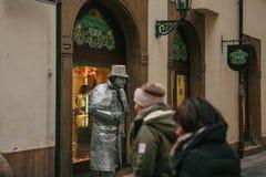 布拉格,捷克- 2016年12月13日:在布拉格街道上站立的人雕象 在街道上的游人 库存图片