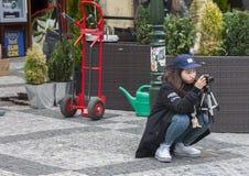 布拉格,捷克- 2017年3月14日:学会注意的学生亚裔女孩摄影师拍爱好的照片,在三脚架的照相机 免版税库存照片