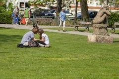 布拉格,捷克- 2011年4月20日:这些男朋友和女朋友坐绿色水多的草 免版税库存照片