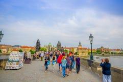 布拉格,捷克- 2015年8月13日, :人们横渡在著名查理大桥的,可看见的雕象在旁边 库存照片