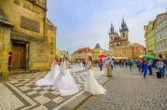 布拉格,捷克- 2015年8月13日, :在城市街道上的三套妇女佩带的婚礼礼服有我们的夫人教会的  免版税库存照片