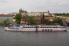 布拉格,捷克- 2017年4月15日:在伏尔塔瓦河河的Sumava小船,有布拉格城堡的在背景中 库存照片