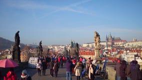 布拉格,捷克- 2016年12月3日 著名查尔斯桥梁和遥远的城堡在一个晴天 走的游人 库存照片