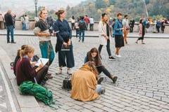布拉格, 2017年10月28日:创造性的女孩-艺术家在布拉格城堡旁边绘在街道上的画 库存图片