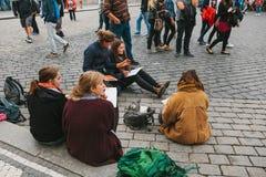 布拉格, 2017年10月28日:创造性的女孩-艺术家在布拉格城堡旁边绘在街道上的画 库存照片