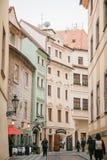 布拉格, 2016年12月13日:圣诞节在布拉格 人们沿狭窄的街道走,在装饰的葡萄酒大厦之间 免版税库存照片