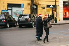 布拉格, 2016年12月24日:圣诞节在布拉格 未知的夫妇-红色新年帽子的走通过的男人和妇女 免版税库存图片