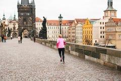 布拉格, 2016年12月24日:女孩运动员安排一个早晨跑在查理大桥的冬天在捷克的布拉格 免版税库存照片