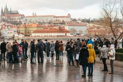 布拉格, 2016年12月24日:小组游人在查理大桥附近站立并且敬佩历史建筑的看法 库存照片