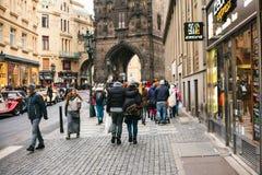 布拉格, 2016年12月24日:旅游业在布拉格 人人群通过美丽的查理大桥走通过商店 免版税库存图片
