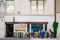 布拉格, 2017年9月18日:街道城市咖啡馆 一套西装的一个人有预定一名的妇女的在桌上谈话和 免版税图库摄影