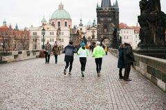 布拉格, 2016年12月24日:运动员安排一个早晨跑在查理大桥的冬天在捷克的布拉格 免版税库存图片