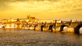 布拉格Hradcany全景在金黄晴天 在伏尔塔瓦河河的查理大桥有布拉格城堡的,捷克 免版税库存图片