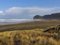 布朗与宽沙丘的沙子海滩 有风Suny天 山在背景中 免版税库存照片