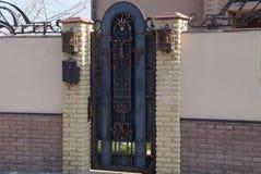 布朗与篱芭的一个伪造的样式和零件的金属门由砖和混凝土制成 免版税图库摄影