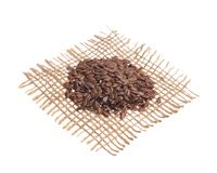布朗亚麻籽 在黑森州的织品,被隔绝的白色后面的五谷 免版税库存照片