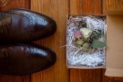 布朗人的鞋子和新郎的钮扣眼上插的花 图库摄影