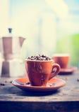 布朗充分浓咖啡杯子在厨房用桌上的咖啡豆与咖啡罐 免版税库存照片
