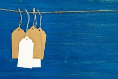 布朗和垂悬在蓝色背景的一条绳索的白色白纸价牌或者标号组 免版税库存照片