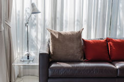 布朗和红色枕头在沙发有灯的 库存图片