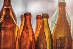 布朗和绿色老玻璃瓶在窗台,与帷幕 特写镜头,白天 免版税图库摄影