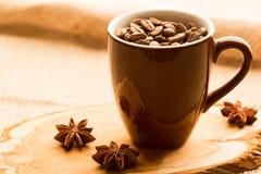 布朗咖啡杯和咖啡豆在木桌上 免版税库存照片